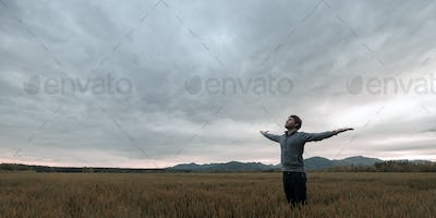 Young man standing in autumn meadow