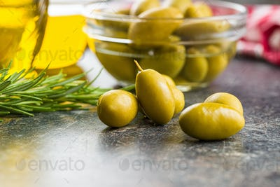Green olives on old kitchen table.