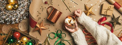 Hot chocolate in female hands and Christmas decoration, wide composition