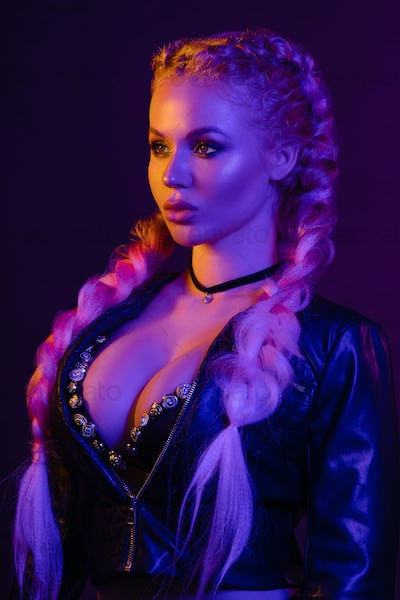 Portrait of seductive young European woman surrounded by evening neon lights medium close-up