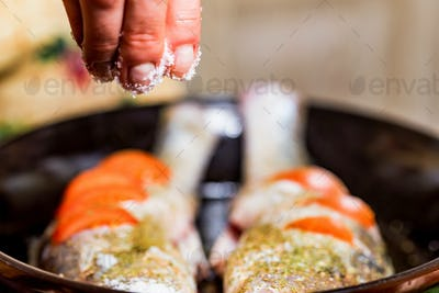 Adding spices to raw zander fish on frying pan
