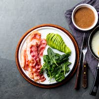 Ketogenic diet breakfast. fried egg, bacon and avocado, spinach and bulletproof coffee.