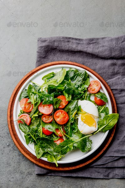 Fresh summer salad with baby spinach, tomatoes cherry and egg.