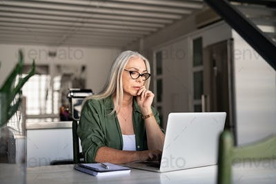 Worried senior woman using laptop
