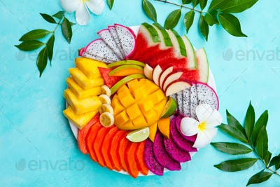 Tropical Fruits Assortment on a Plate. Blue Background. Top View. Copy Space.