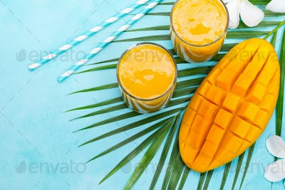 Fresh Tropical Fruit Smoothie Mango Juice and Fresh Mango on Blue Background. Copy Space. Top View.