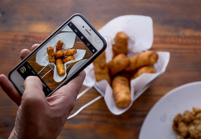 Men hands taking food photo of VENEZUELAN TEQUENOS by mobile phone