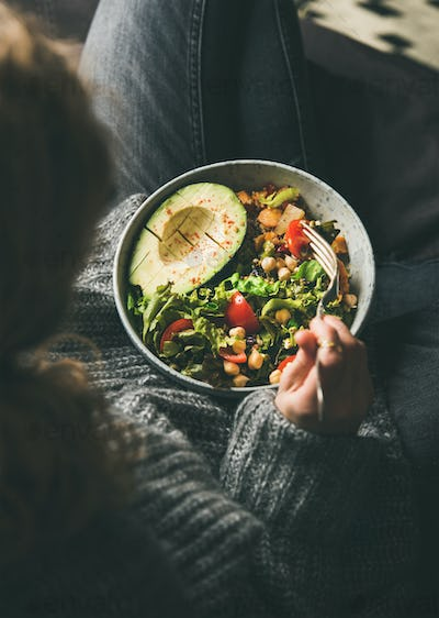 Woman eating healthy vegetarian dinner from Buddha bowl, top view