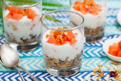 Dessert with Papaya, Yogurt and Granola in Glasses. Blue Textile Background.