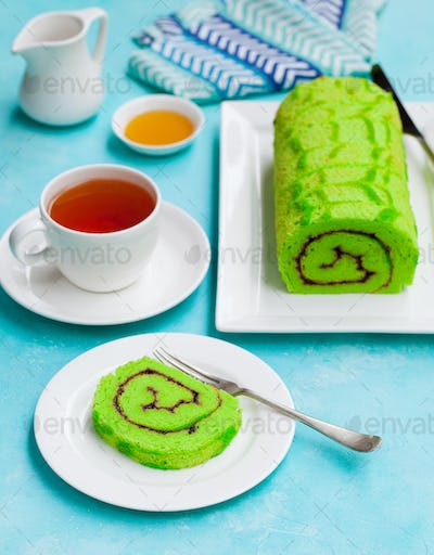 Green Roll Cake With a Cup of Tea on Blue Background.