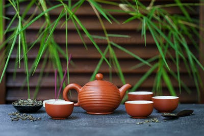Green Tea in Tea Pot and Chawan Bowls, Cups on Slate Background. Copy Space.