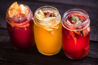 Three glass jars with delicious hot winter beverages close