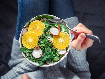 Woman in jeans at bed, holding vegan salad bowl