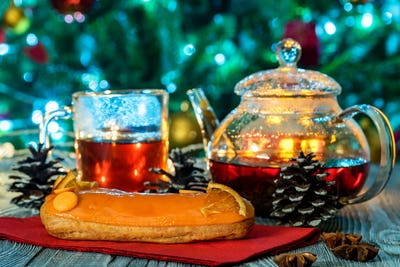 Cozy still life with tea, candle light and eclairs