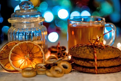 Cozy still life of tea, christmas light and pastry