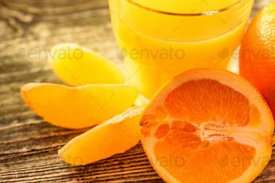 Oranges and orange juice on a wooden background