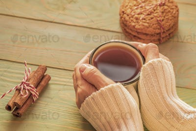 Woman in sweater holds cup of tea on wooden table