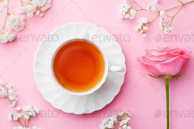 Cup of Tea with Fresh Flowers on Pink Background. Copy Space. Top View.