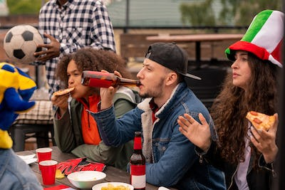 Football fans drinking beer and eating pizza while watching play of their team