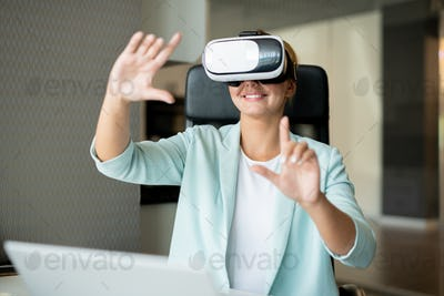 Happy young creative woman in smartcasual pointing at virtual display