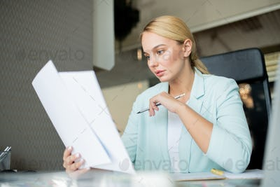 Young serious teacher with pencil checking papers of students