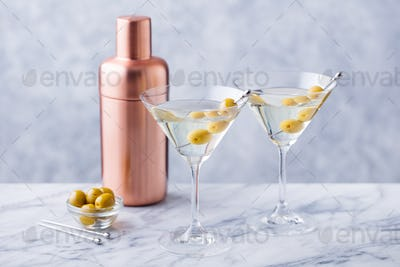 Martini Cocktail with Green Olives, Shaker on Marble Table Background. Copy space.
