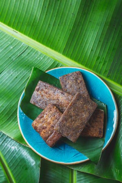 Easter Island Tahitian Polynesian banana pie pupping POE on blue plate on banana palm tree leaves.