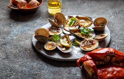 Raw seafood, crabs, clams and mussels shellfish with lemon and cilantro on gray plate.