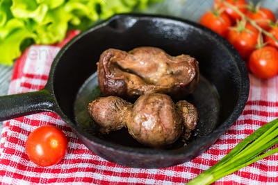 Tasty roasted chicken giblets in pan