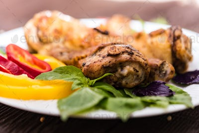 Roasted chicken quarter legs on rustic background