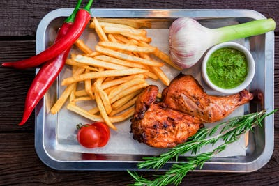 Top view meal with chicken thigh, french fries, chili pepper and garlic