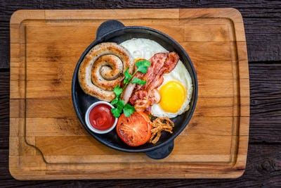 Top view meal with fried egg, sausage, bacon, tomato and sauce in frying pan