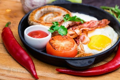 Nutritious meal with fried egg, sausage, bacon, tomato and sauce in frying pan