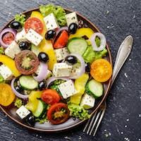 Top view at Mediterranean diet dish greek salad on slate tray