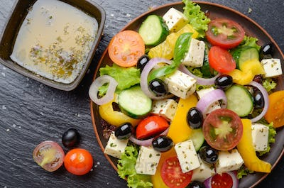 Top view at Mediterranean diet dish greek salad on slate tray wi