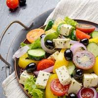 Top view at Mediterranean diet dish greek salad on vintage metal
