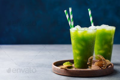 Matcha Ice Tea in Tall Glass on Wooden Plate. Blue Background. Copy Space.