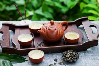 Green Tea in Tea Pot and Bowls, Cups on a Wooden Tray. Outdoor Background.
