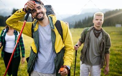 Group of friends on a mountain. Men and women climbing rocks