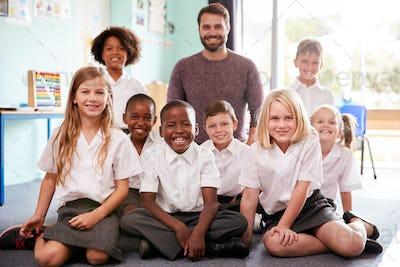 Portrait Of Elementary School Pupils Wearing Uniform Sitting On Floor In Classroom With Male Teacher