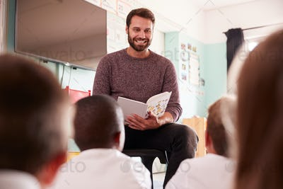 Male Teacher Reading Story To Group Of Elementary Pupils Wearing Uniform In School Classroom