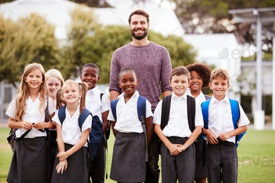 Outdoor Portrait Of Elementary School Pupils With Teacher Wearing Uniform Standing On Playing Field