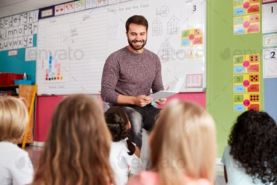 Male Teacher Reading Story To Group Of Elementary Pupils In School Classroom