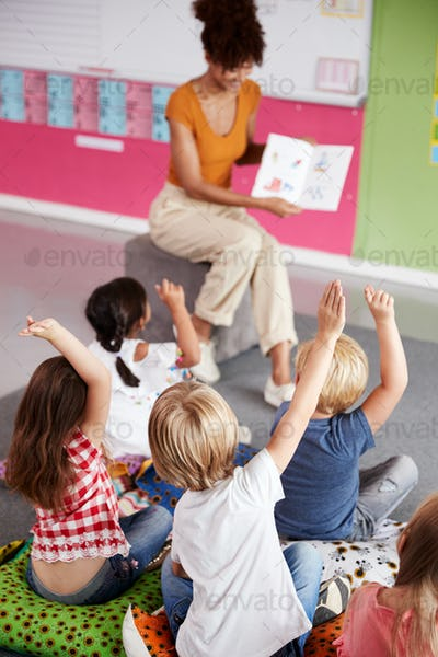 Elementary Pupils Raising Hands To Answer Question As Female Teacher Reads Story In Classroom