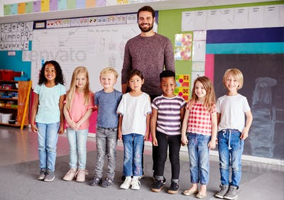 Portrait Of Elementary School Pupils Standing In Classroom With Male Teacher