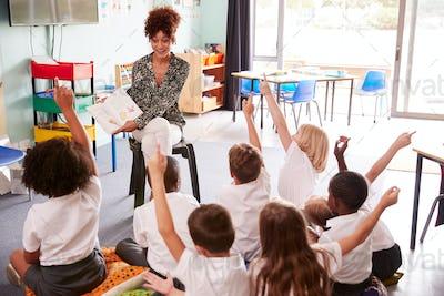 Elementary Pupils Wearing Uniform Raise Hands To Answer Question As Female Teacher Reads Book