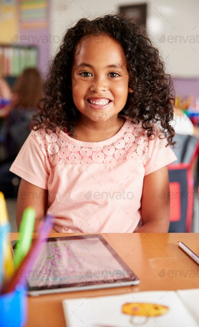 Portrait Of Female Pupil In Elementary School Drawing Using Digital Tablet In Classroom