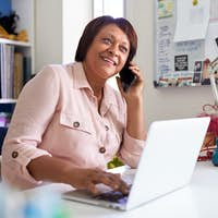 Mature Woman With Laptop Working In Home Office Using Mobile Phone