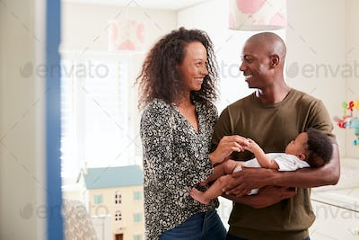 Loving Parents Standing In Nursery Cuddling Baby Son At Home