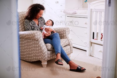 Loving Mother Sitting In Chair Cuddling Baby Son In Nursery At Home